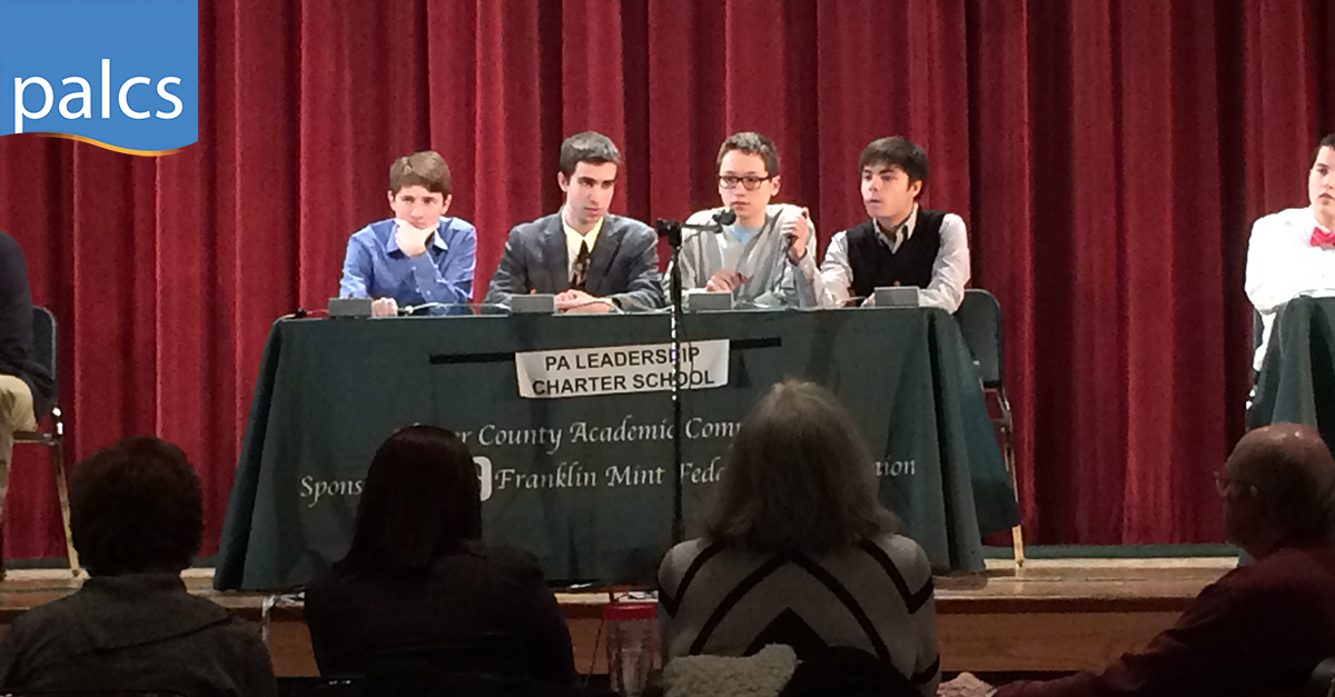 four USP students sitting at a table with a microphone