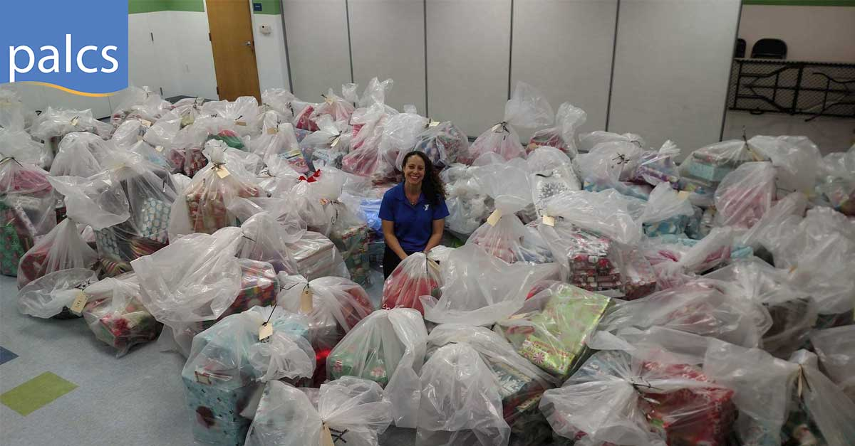 Charity work, staff members sponsor gifts for children, a teacher surrounded by bags of wrapped presents