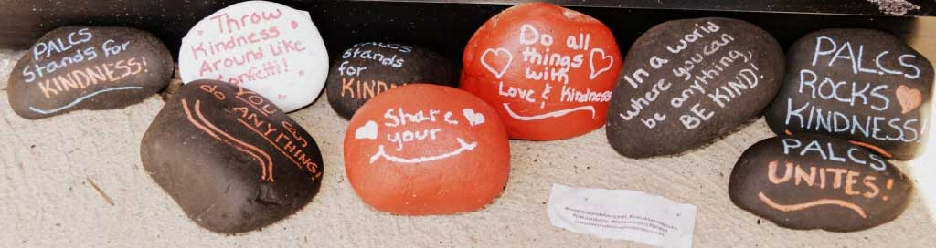 painted rocks with motivational sayings: palcs stands for kindness, throw kindness around like confetti, you can do anything, share your smile, do all things with love and kindness, in a world where you can be anything, be kind, palcs kindness rocks, palcs unites