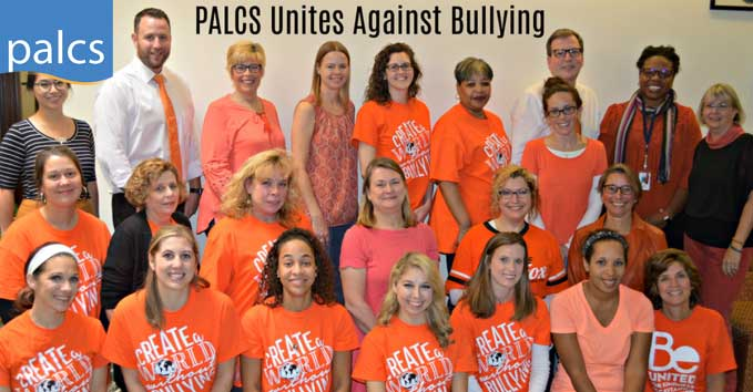 two dozen staff members in the palcs west chester office wearing orange shirts