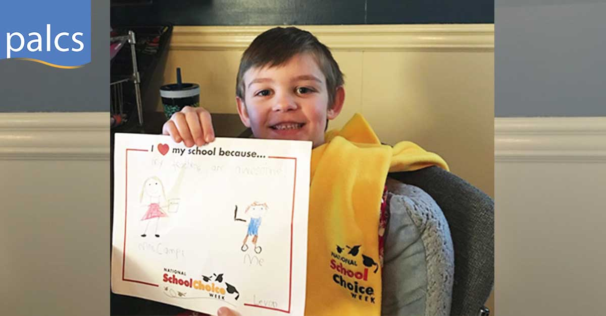 Levon holding a drawing saying I love my school because my teachers are awesome