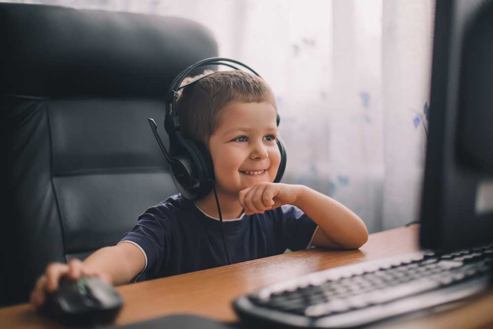 Little boy in headphones working with a mouse at PALCS Elementary School