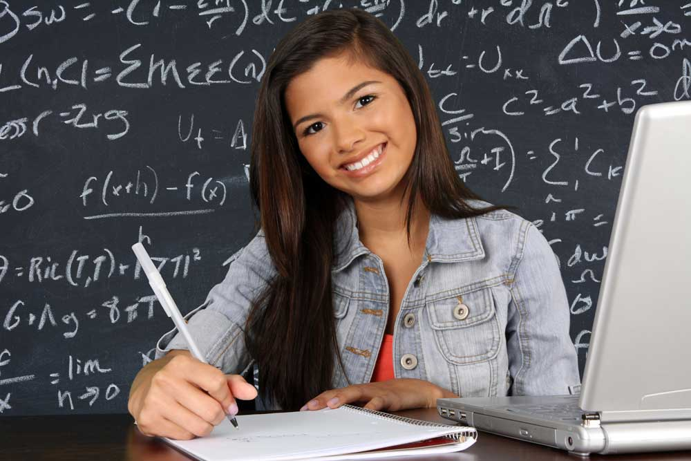Student in front of blackboard using laptop
