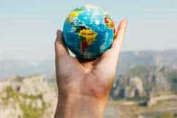 Hand holding globe in front of mountain