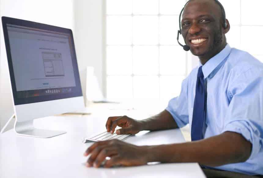 Man on computer with headset for online information session